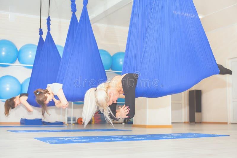 Giovani donne che fanno esercizio aereo di yoga o yoga antigravità fotografie stock