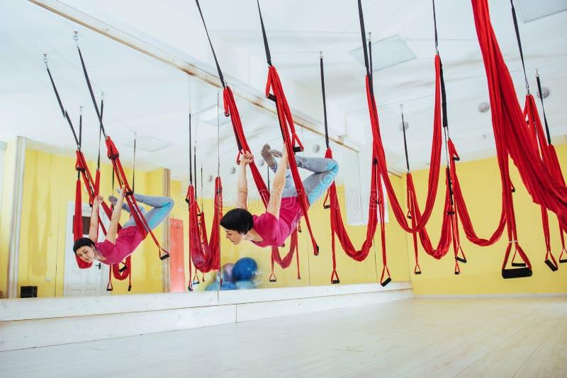 Giovani donne che fanno esercizio di yoga o yoga aerea antigravità nello studio fotografia stock libera da diritti