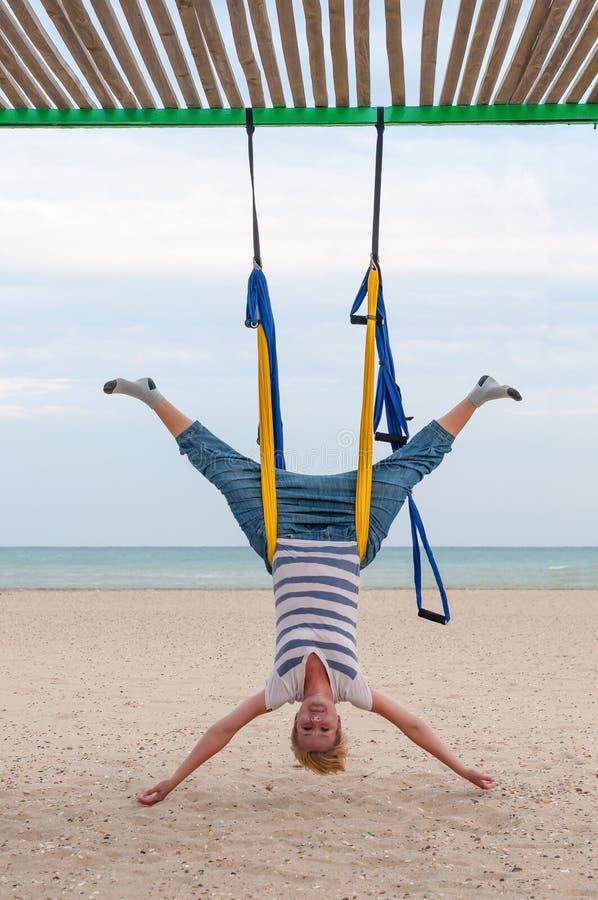 Giovani donne che fanno i asanas aerei di yoga o yoga antigravità dell'interno Volo, forma fisica, allungamento, equilibrio, eser fotografia stock libera da diritti