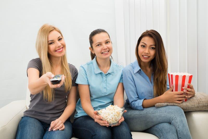 Giovani donne che guardano televisione immagini stock