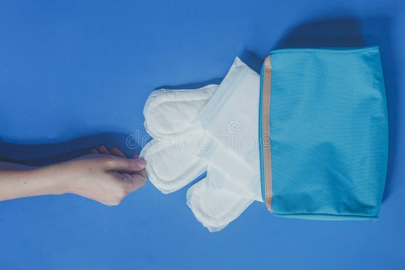 Giovani donne che prendono i cuscinetti sanitari dentro della sua borsa cosmetica su fondo blu immagini stock