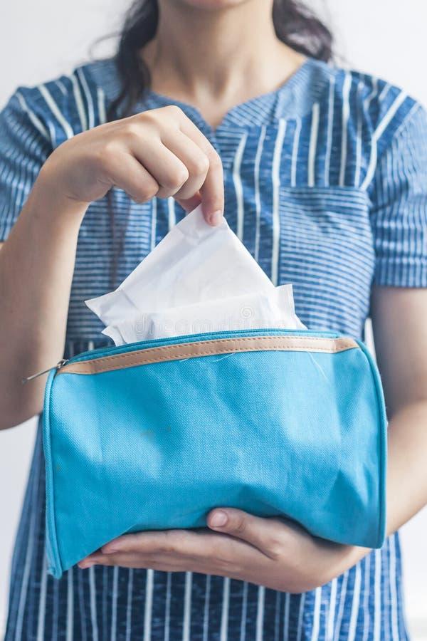Giovani donne che prendono i cuscinetti sanitari dentro della sua borsa cosmetica su fondo blu immagine stock