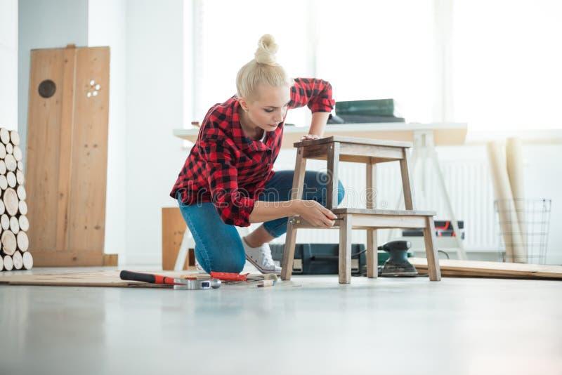 Giovani donne che riparano mobilia a casa immagini stock