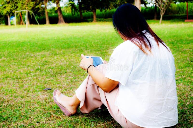 Giovani donne che usando il ipad della tavola mentre sedendosi sull'erba nel parco, fotografia stock libera da diritti