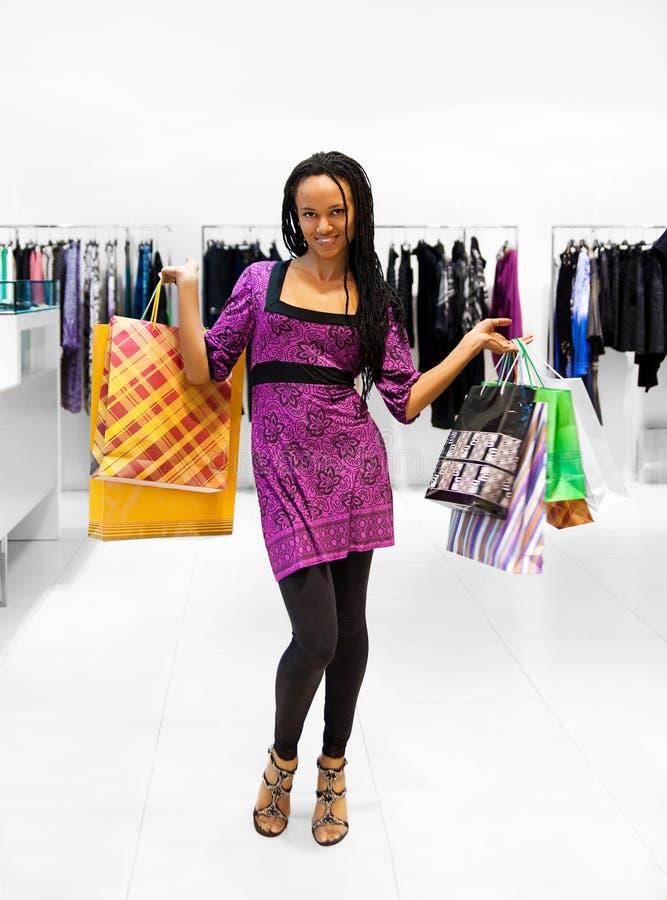 Giovani donne con i pacchetti nel negozio fotografie stock