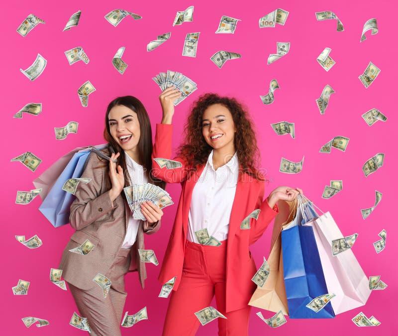 Giovani donne con i sacchetti di acquisto e dei soldi fotografia stock