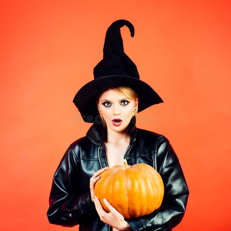 Giovani donne in costumi neri di Halloween della strega sul partito sopra fondo rosso Strega che posa con la zucca immagini stock libere da diritti