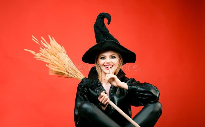 Giovani donne in costumi neri di Halloween della strega sul partito sopra fondo rosso Scopa o manico di scopa della tenuta della  fotografie stock