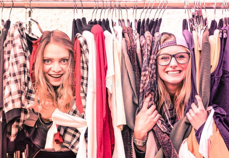 Giovani donne dei pantaloni a vita bassa al mercato delle pulci dei vestiti - divertimento dei migliori amici fotografia stock libera da diritti