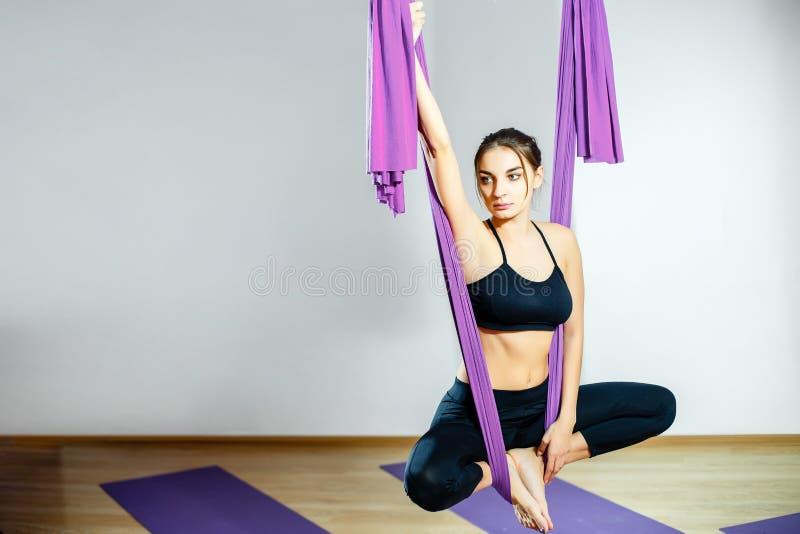 Giovani donne del ritratto che fanno gli esercizi antigravità di yoga Allenamento aereo aereo dell'istruttore di forma fisica del fotografie stock libere da diritti