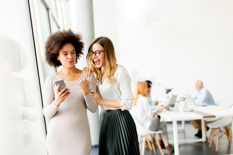 Giovani donne di affari multirazziali che sorridono, mentre l'altro businesspeo fotografia stock