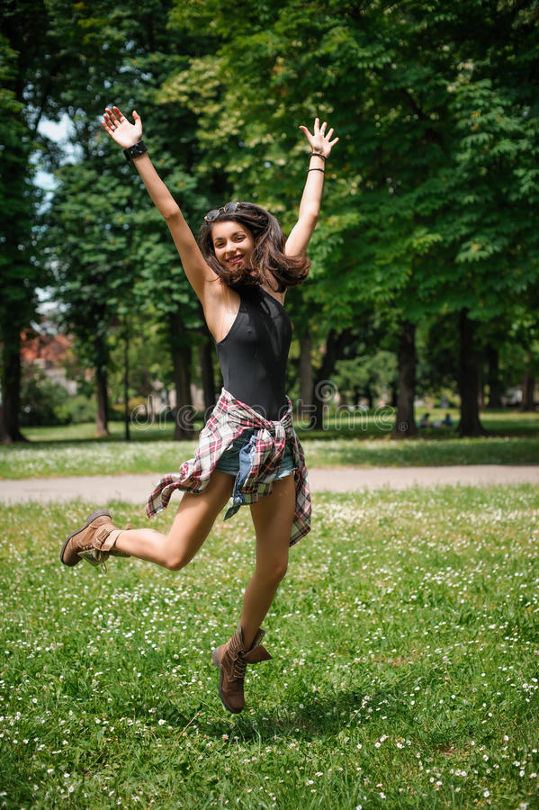 Giovani donne divertendosi e saltando nella foresta un giorno soleggiato immagini stock
