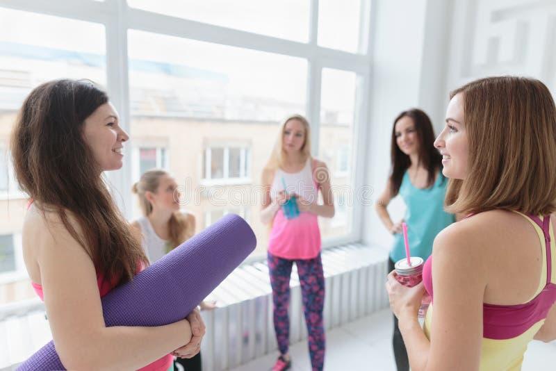 Giovani donne felici che chiacchierano prima della loro classe di yoga fotografia stock libera da diritti