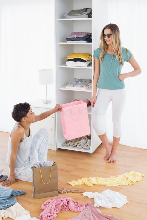 Giovani donne felici che sistemano i vestiti in scaffale immagine stock