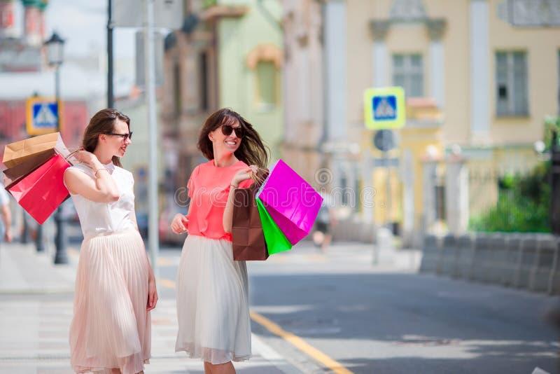 Giovani donne felici con i sacchetti della spesa che camminano lungo la via della città Vendita, consumismo e concetto della gent immagine stock libera da diritti