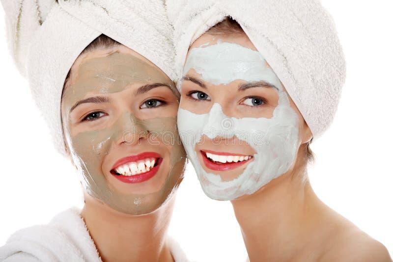 Giovani donne felici con la mascherina facciale dell'argilla fotografie stock