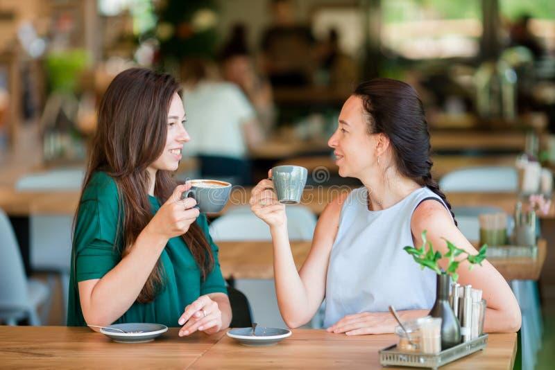 Giovani donne felici con le tazze di caffè al caffè all'aperto Concetto di amicizia e di comunicazione fotografia stock