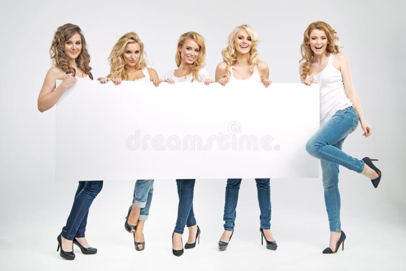 Giovani donne graziose che tengono il bordo fotografie stock libere da diritti