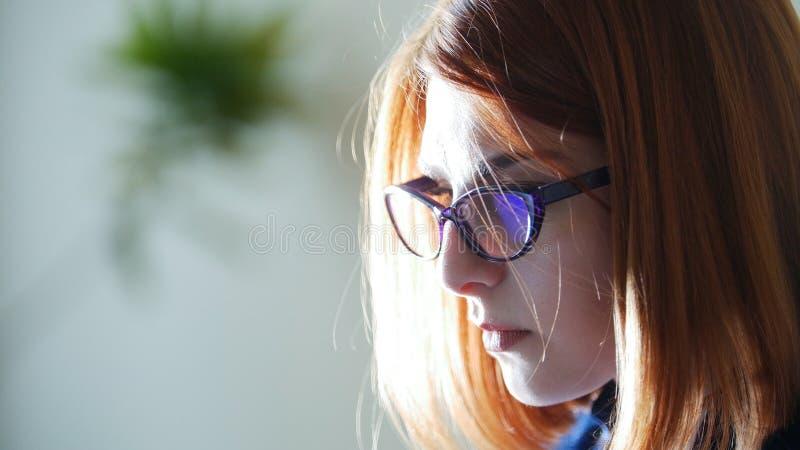 Giovani donne rosse del officeworker dei capelli in vetri sui precedenti bianchi immagini stock libere da diritti