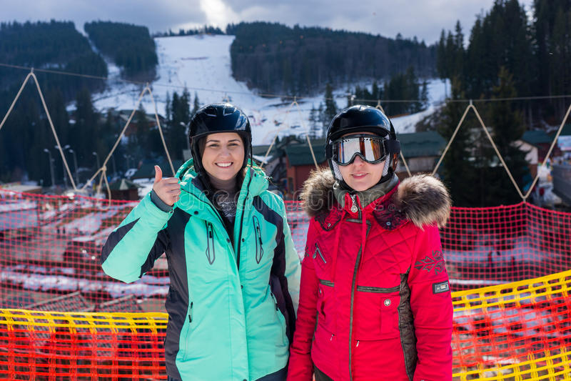 Giovani donne sorridenti in vestiti di sci, con i caschi e gli occhiali di protezione s dello sci fotografie stock libere da diritti