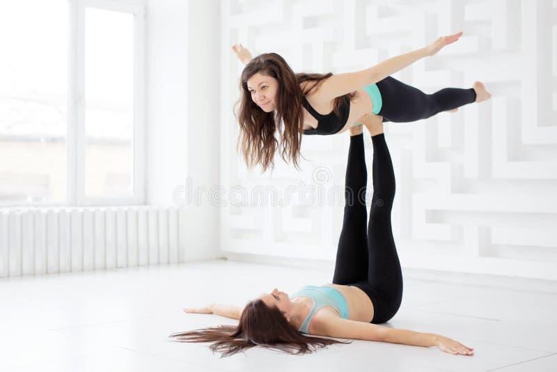 Giovani donne sportive che fanno acroyoga fotografia stock