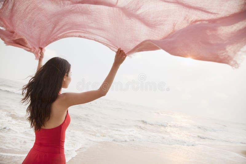 Giovani donne sulla sciarpa della tenuta della spiaggia nell'aria e nell'esaminare la distanza immagine stock