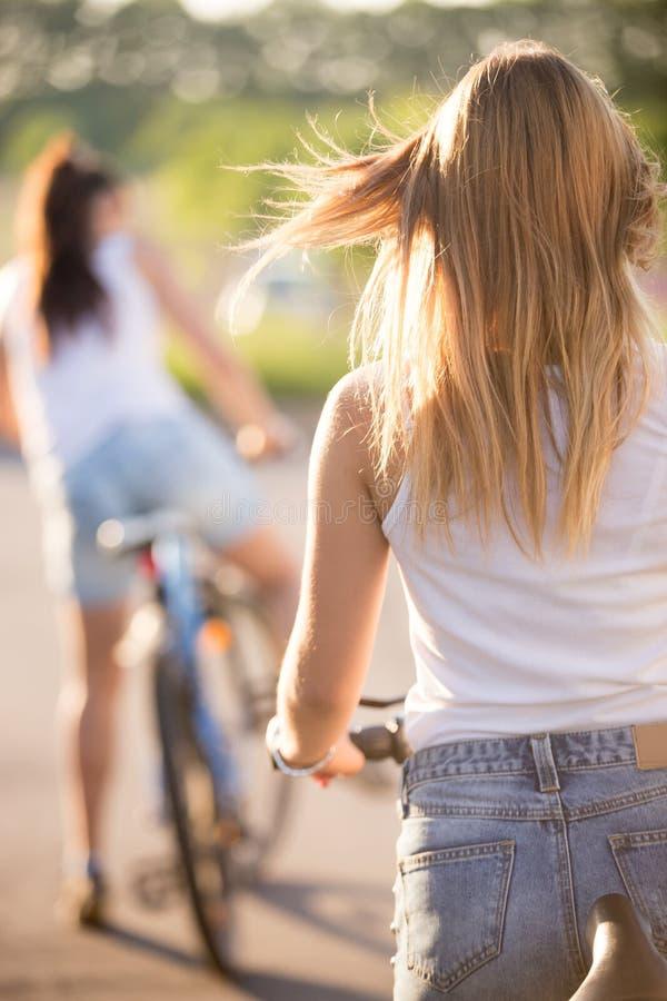 Giovani donne sulle biciclette, retrovisione fotografia stock libera da diritti