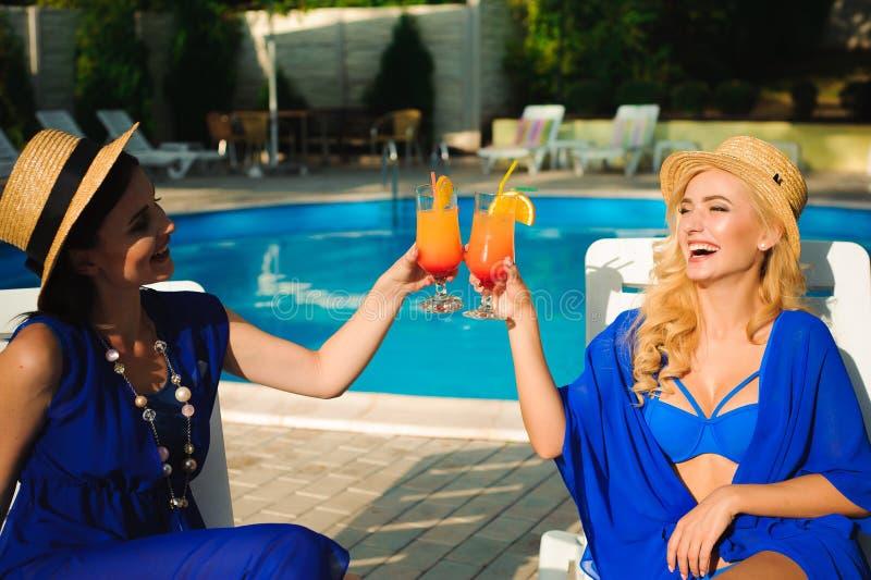 Giovani donne sveglie felici con i cocktail che ridono e che si divertono vicino alla piscina fotografie stock libere da diritti