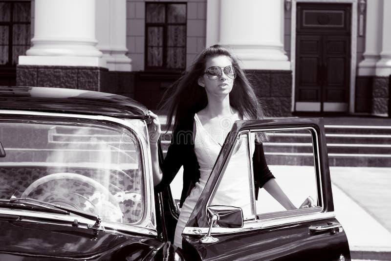 Giovani donne vicino alla retro automobile fotografia stock