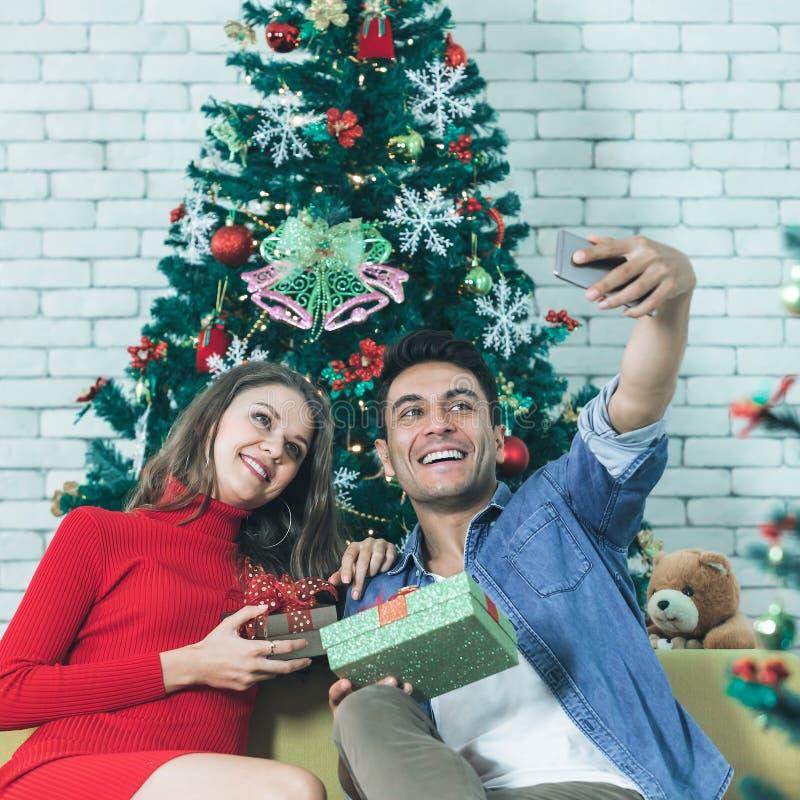Giovani e belle coppie caucasiche che si siedono sull'felice del sofà fotografie stock