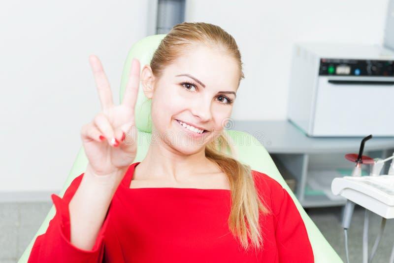 Giovani e paziente abbastanza femminile al dentista che mostra gestu di vittoria fotografia stock