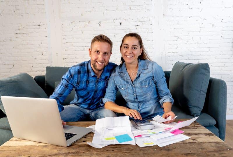 Giovani giovani fatture di pagamento felici delle coppie con il computer portatile che ritiene fortunato e fortunato fuori dai de fotografia stock libera da diritti