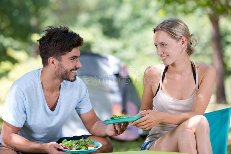 Giovani felici che mangiano insalata sana per pranzo immagine stock