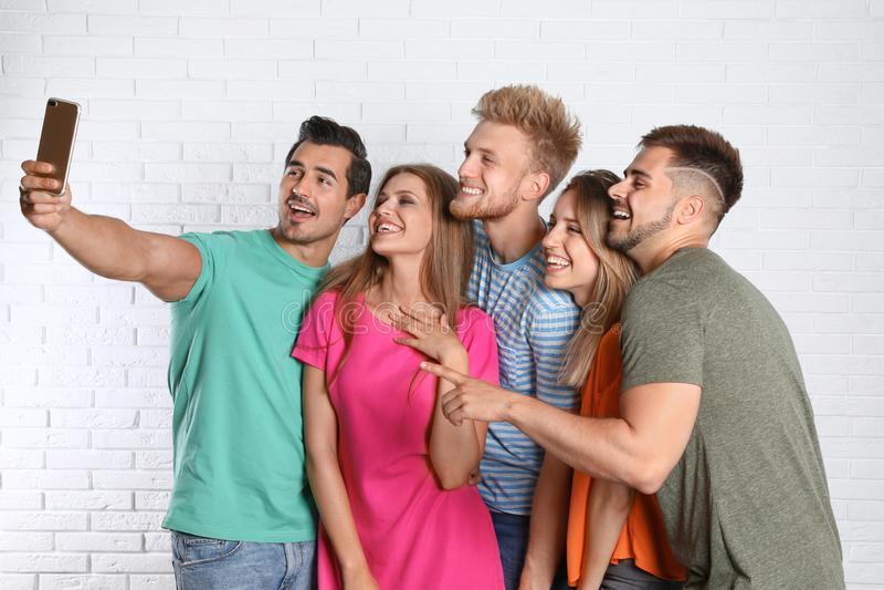 Giovani felici che prendono selfie vicino alla parete bianca immagine stock libera da diritti