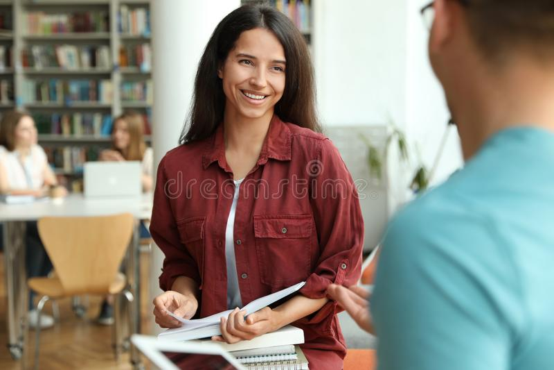 Giovani felici con la conversazione dei libri fotografia stock