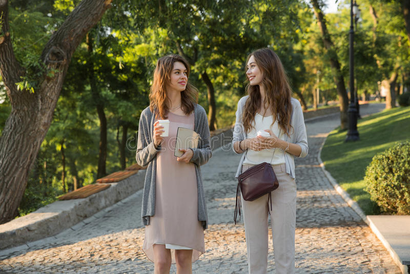 Giovani felici due donne che camminano all'aperto in caffè bevente del parco immagini stock
