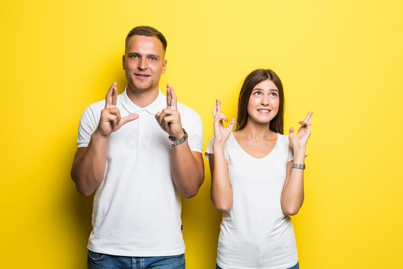 Giovani femminile e maschio chiudendo i loro occhi che attraversano le dita con speranza mentre prevedendo le notizie importanti  immagine stock libera da diritti