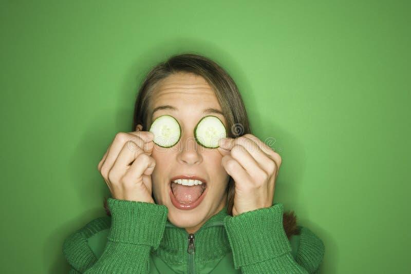 Giovani fette caucasiche del cetriolo della holding della donna sopra i suoi occhi. fotografia stock