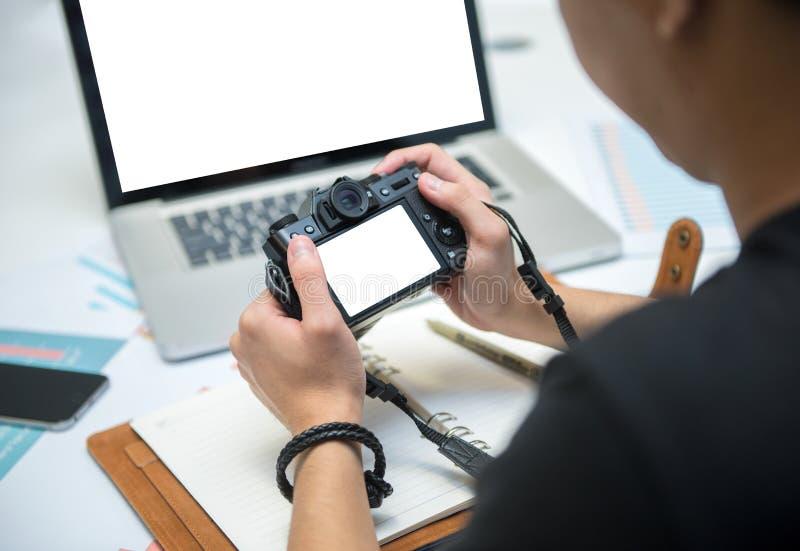 Giovani fotografi che esaminano monitor in bianco sulla macchina fotografica a della macchina fotografica fotografia stock