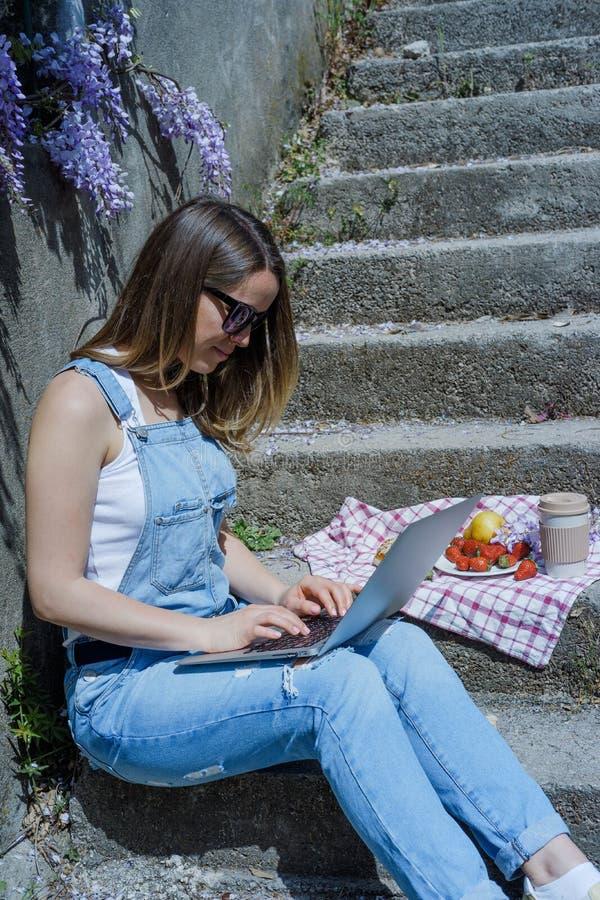 Giovani free lance bionde della donna dei pantaloni a vita bassa in occhiali da sole che funzionano alla l immagine stock