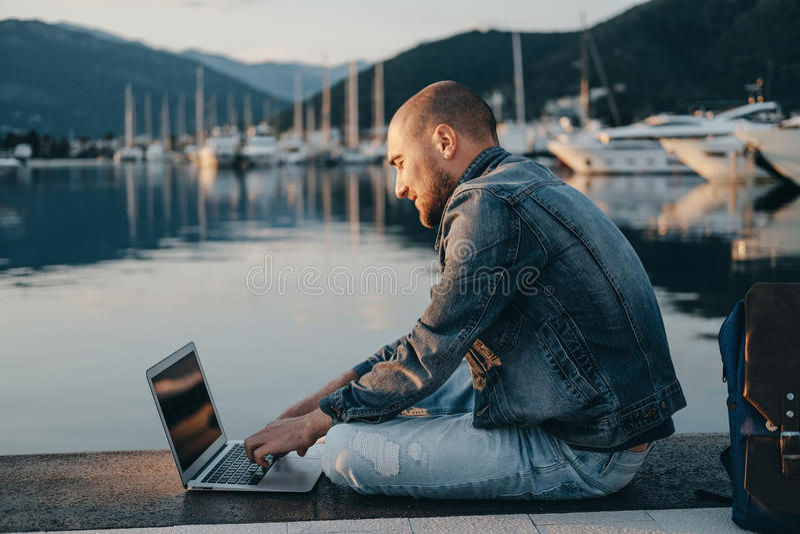 Giovani free lance dell'uomo dei pantaloni a vita bassa che lavorano con il computer portatile che si siede vicino al Se immagini stock