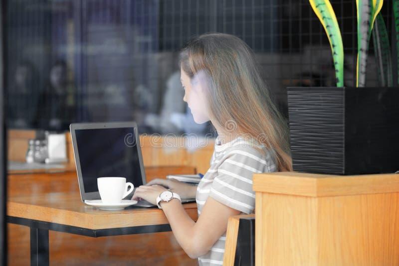Giovani free lance femminili con funzionamento in caffè, vista del computer portatile attraverso la finestra di vetro immagini stock