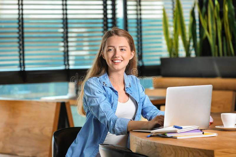 Giovani free lance femminili con funzionamento del computer portatile in caffè fotografia stock libera da diritti