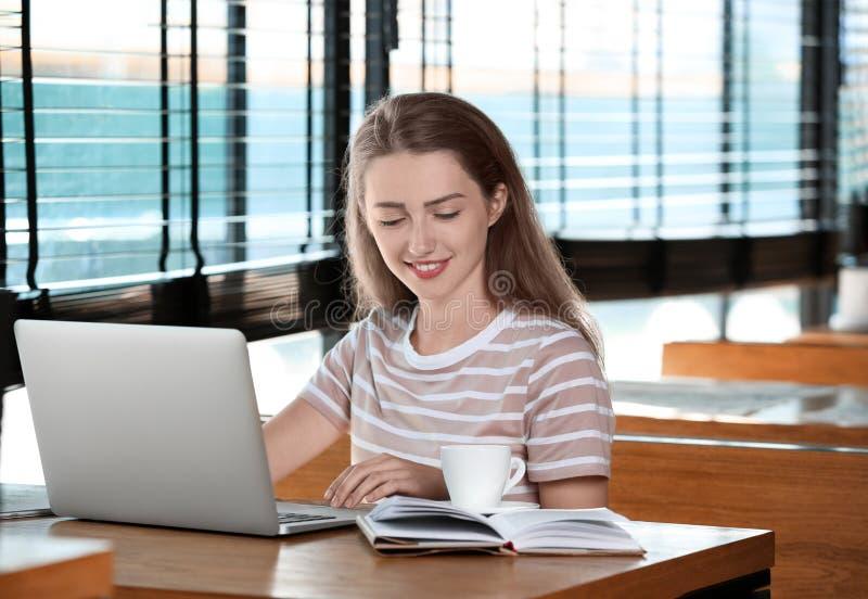 Giovani free lance femminili con funzionamento del computer portatile in caffè fotografie stock libere da diritti