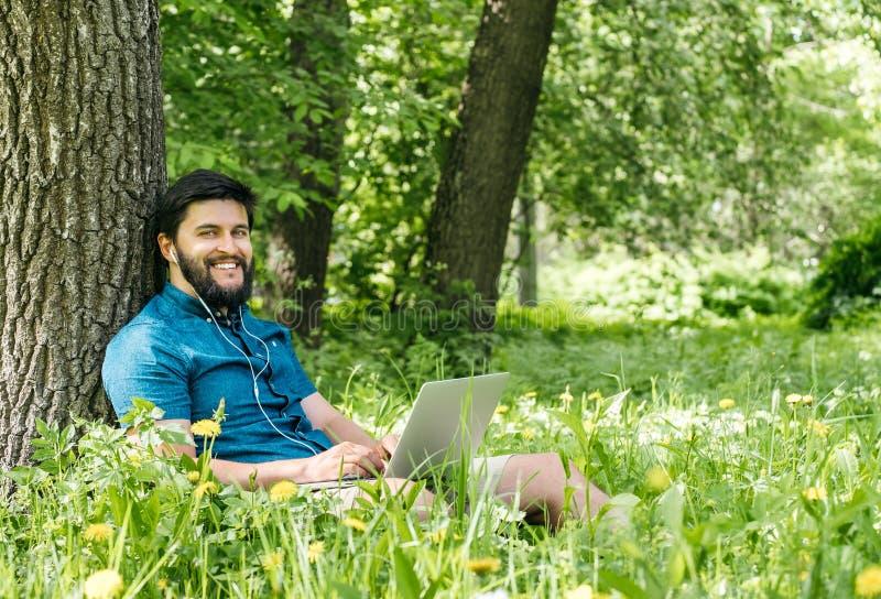 Giovani free lance moderne dell'uomo d'affari che lavorano al computer e al sitt fotografia stock