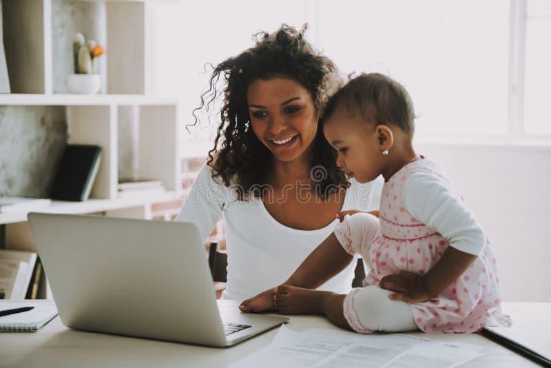 Giovani free lance sorridenti con la figlia a casa immagine stock