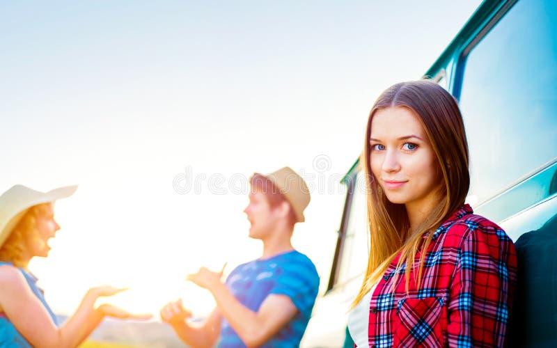 Giovani frieds con l'esterno campervan in natura soleggiata verde fotografie stock libere da diritti