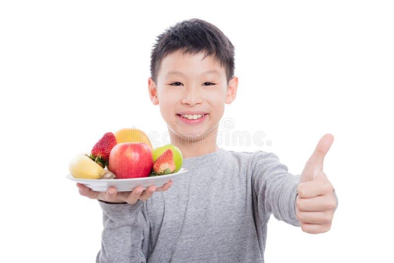 Giovani frutti e sorrisi asiatici della tenuta del ragazzo fotografia stock