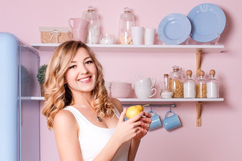 Giovani frutti felici di cibo della donna a casa nella cucina Bella ragazza bionda che mangia la sua prima colazione prima di and fotografia stock libera da diritti
