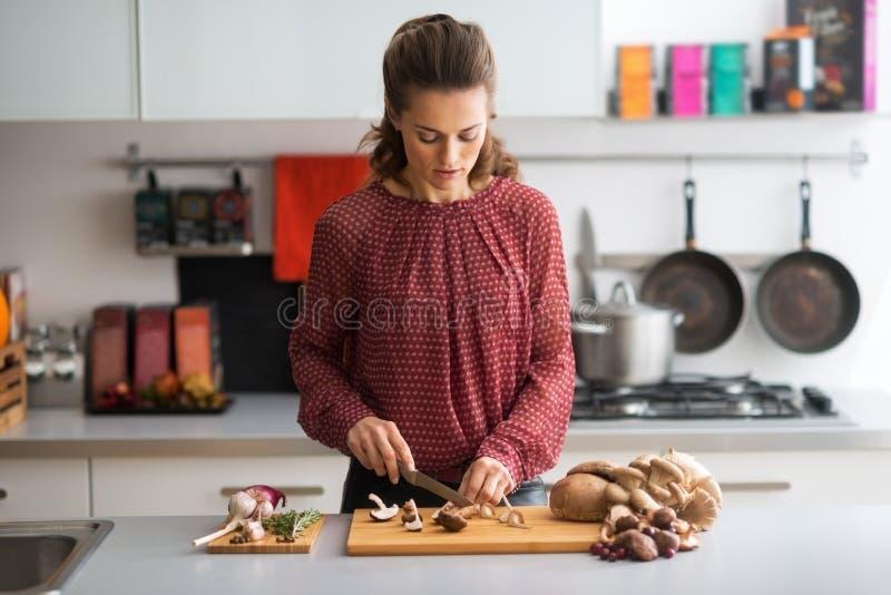 Giovani funghi di taglio della casalinga in cucina fotografia stock